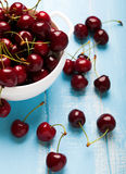 Cherries in a bowl on the blue wooden background close up Stock Images
