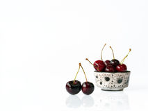 Cherries in bowl on white background. Fresh cherries with water drops in a little bowl and placed on a white background Stock Images