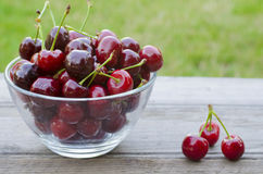 Cherries in bowl and on wood. En background Royalty Free Stock Photos