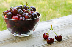 Cherries in bowl and on wood. En background Stock Image