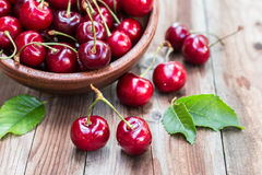 Cherries in bowl on wooden background stock image