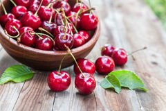 Cherries in bowl on wooden background stock photos