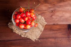 Cherries in a bowl on wooden table. Cherries in a glass bowl on wooden table Royalty Free Stock Images