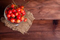Cherries in a bowl on wooden table. Cherries in a glass bowl on wooden table Stock Photos