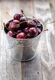 Cherries in a Bucket on a Wooden Table Royalty Free Stock Photos