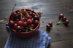 Cherries. Cherry. Cherries in color bowl and kitchen napkin. Royalty Free Stock Image