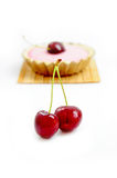 Cherries with cherry tart in the background. Couple of cherries with cherry tart in the background Royalty Free Stock Photography
