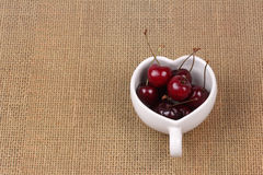 Cherries Chile and Heart-shaped mug on sackcloth. Royalty Free Stock Photos
