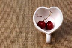 Cherries Chile and Heart-shaped mug on sackcloth. Stock Photography