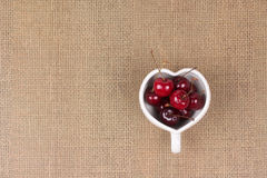 Cherries Chile and Heart-shaped mug on sackcloth. Royalty Free Stock Photography