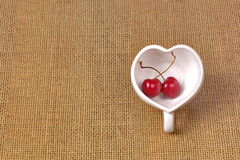 Cherries Chile and Heart-shaped mug on sackcloth. Stock Photography
