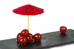 Cherries. Conceptual image , loneliness, isolation, rejection, and abandonment, not fitting in, showing a group of cherries together with one single cherry Stock Images