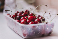 Cherries in a container. Ripe washed cherry in a container on a white table, fresh harvest Royalty Free Stock Images