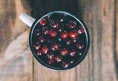Cherries In Cup. Fresh cherries in an old metal mug on rustic wooden table.n Royalty Free Stock Images