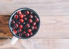Cherries In Cup. Fresh cherries in an old metal mug on rustic wooden table.n Stock Image