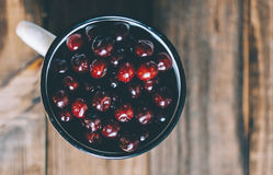 Cherries In Cup. Fresh cherries in an old metal mug on rustic wooden table.n Stock Photography