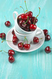 Cherries in cup. On turquoise wooden background Royalty Free Stock Photography