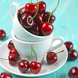 Cherries in cup. On turquoise wooden background Stock Images
