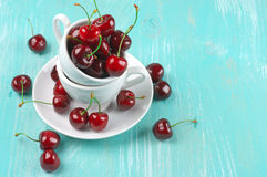 Cherries in cup. On turquoise wooden background Royalty Free Stock Images