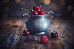 Cherries. Cup of cherries on wood rustic background stock image