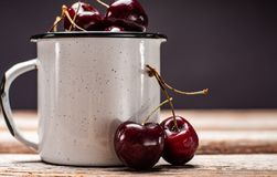 Cherries in the cup on wooden table. Fresh ripe cherries. Cherries in the cup on wooden table Royalty Free Stock Image
