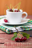 Cherries in the cup on wooden table. Cherries in the white cup on wooden table Royalty Free Stock Image