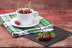 Cherries in the cup on wooden table. Cherries in the white cup on wooden table Royalty Free Stock Images