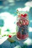 Cherries and currants in a jar on blue table Royalty Free Stock Photo