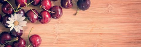 Cherries and daisy on wood background with copy space Royalty Free Stock Photo