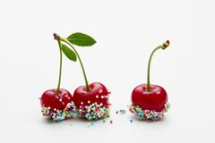 Cherries decorated with colorful candy sprinkles. Sprinkle covered cherry. Three red cherries, decorated with colorful candy sprinkles, on white background Royalty Free Stock Photos