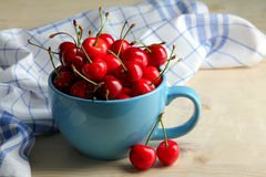 Cherries. Delicious bunch of cherries in cup near napkin on a wooden background Stock Image