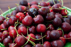 Cherries in a dish on a bamboo mat Stock Photo