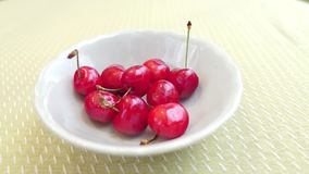 Cherries falling into a white bowl stock video footage