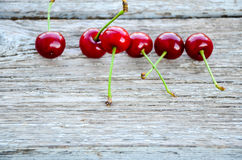 Cherries. Fresh organic red cherries with stems  on wooden background Royalty Free Stock Image