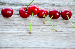 Cherries. Fresh organic red cherries with stems  on wooden background Royalty Free Stock Photography