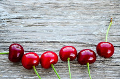 Cherries. Fresh organic red cherries with stems  on wooden background Royalty Free Stock Photo