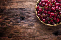 Cherries. Fresh sweet cherries. Delicious cherries with water drops in retro bowl on old oak table Royalty Free Stock Images