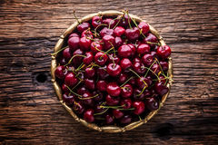 Cherries. Fresh sweet cherries. Delicious cherries with water drops in retro bowl on old oak table Stock Image