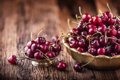 Cherries. Fresh sweet cherries. Delicious cherries with water drops in retro bowl on old oak table Stock Photos