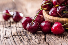 Cherries. Fresh sweet cherries. Delicious cherries with water drops in retro bowl on old oak table Stock Images