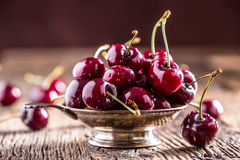 Cherries. Fresh sweet cherries. Delicious cherries with water drops in retro bowl on old oak table.  royalty free stock photo