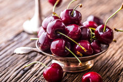 Cherries. Fresh sweet cherries. Delicious cherries with water drops in retro bowl on old oak table Stock Photo