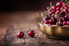 Cherries. Fresh sweet cherries. Delicious cherries with water drops in retro bowl on old oak table Royalty Free Stock Image