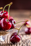 Cherries. Fresh sweet cherries. Delicious cherries with water drops in retro bowl on old oak table Stock Photography