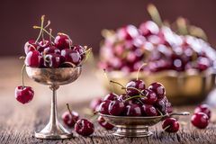 Cherries. Fresh sweet cherries. Delicious cherries with water drops in retro bowl on old oak table Royalty Free Stock Photos