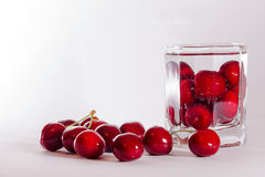 Cherries in glass and a handful of cherries beside Stock Image