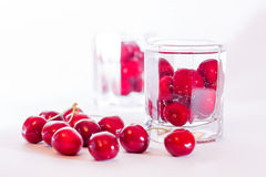 Cherries in glass and a handful of cherries beside Stock Images