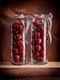 Cherries in glass jars. On wooden table and dark background Royalty Free Stock Photography