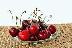 Cherries on glass plate. Cherries on a glass plate over a straw mat Royalty Free Stock Photography