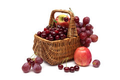 Cherries, grapes and apples in a basket on a white background Royalty Free Stock Images
